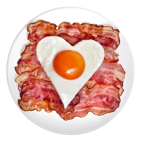 bacon love: fried bacon with egg in shape of heart on a plate top view surface isolated on white background