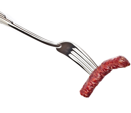 smoked sausage on a fork against white background photo