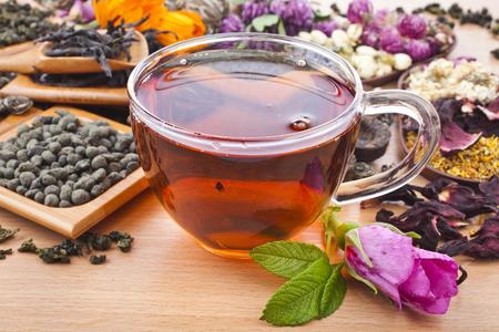 Taza de cristal de té y colección de diferentes tipos seco de té verde, negro, a base de hierbas en la cocina de madera fondo de la tabla