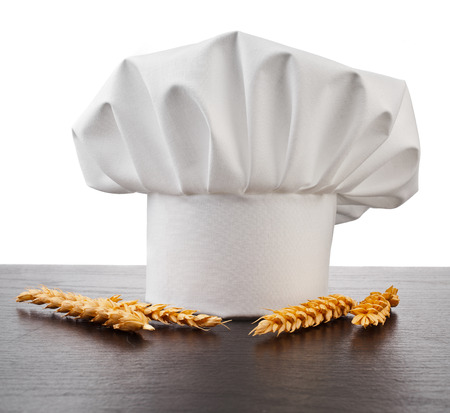 Chef Hat and Wheat Ears isolated on black table background photo