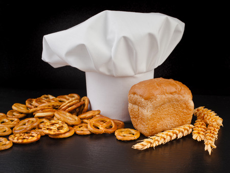 Wheat Ears, Bread and Chef Hat on black table background photo