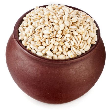clay pot: barley pearl porridge in a clay pot isolated on white background Stock Photo