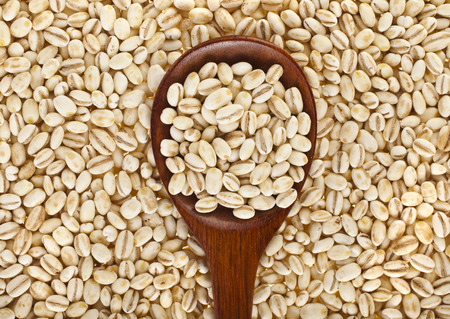pearl barley with wooden spoon close up surface top view background