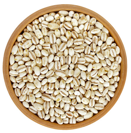 pearl barley: Pearl barley grains heap in bowl top view surface close up isolated on white background Stock Photo