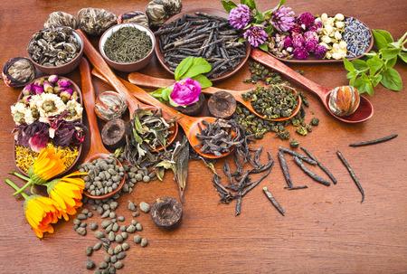 flores secas: té variedad surtido en cuchara de madera en la cocina de madera fondo de la tabla Foto de archivo