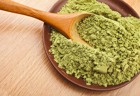 dry powder: Powdered Green Tea Matcha in spoon on wood table surface close up background