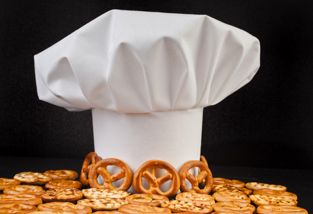 Chef Hat and pretzels isolated on black table background photo