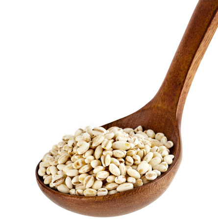 pearl barley: pearl barley in a wooden spoon isolated on white background