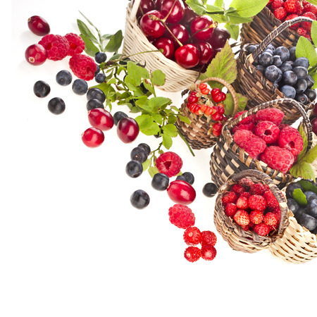 Assortment mix of summer fresh forest berries in the basket isolated on white background photo