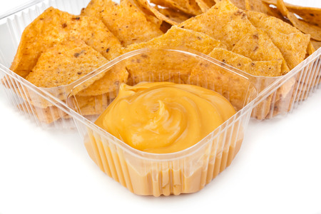 NACHO: nachos chips with cheese sauce in plastic container on white background