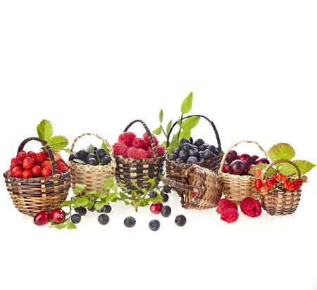 fresh forest mix berries : blueberries , raspberries and strawberries in the basket isolated on white background photo