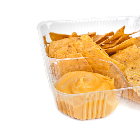 nachos chips with cheese sauce in plastic container close up isolated on white background