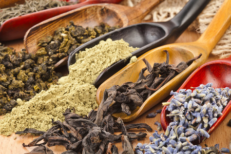 assortment of dry tea in scoops close up on wooden background photo
