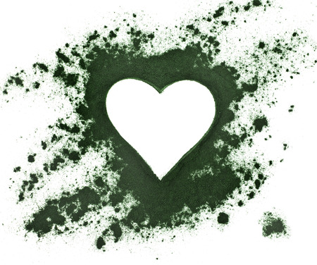 Spirulina powder - algae, nutritional supplement, shape heart surface top view isolated on white background Stockfoto