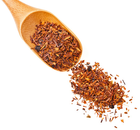 Rooibos tea heap in a wooden scoop , isolated on white background