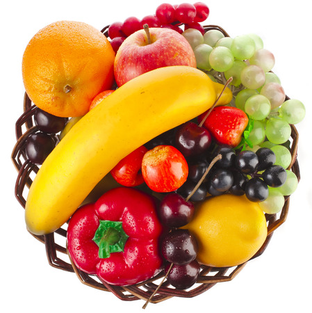 assorted fruits in wicker basket top view surface isolated on white photo