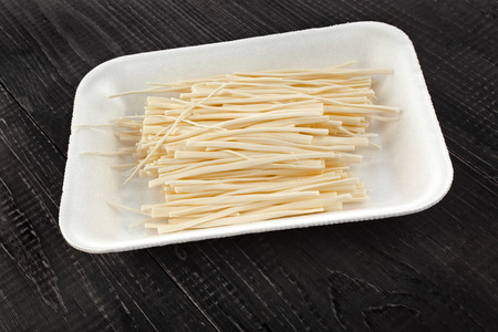 rennet: cheese spaghetti on wooden table surface
