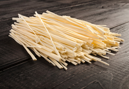 rennet: rennet cheese spaghetti snack on wooden table surface Stock Photo