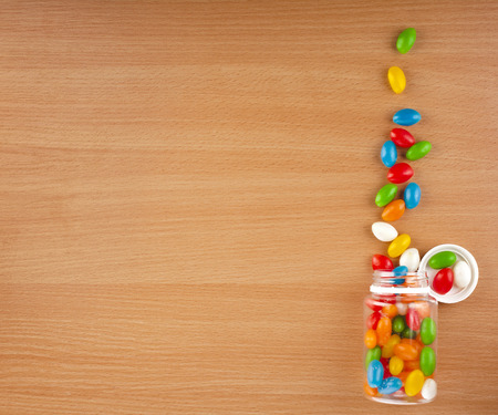 Colored JellyBeans Pills spilled from a bottle on surface wooden table. top view photo