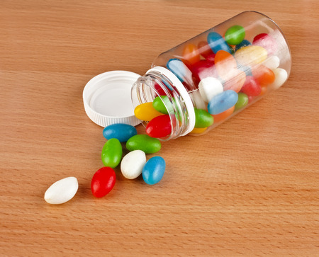Colored Pills pouring out of the plastic bottle on surface wooden table photo