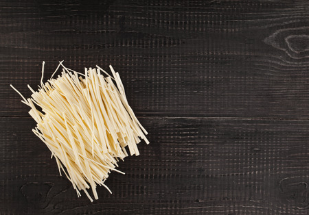 rennet: rennet cheese spaghetti on wooden table surface top view Stock Photo