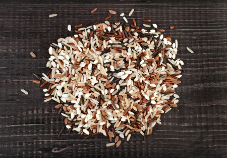colorful blend of several varieties whole grain rice in a rustic wooden surface background photo