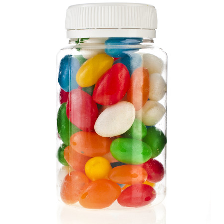 Colored JellyBeans in the plastic bottle isolation on a white background photo