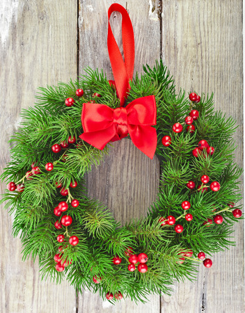 christmas holly: Christmas decoration fir wreath with red berries on wooden door sutface texture