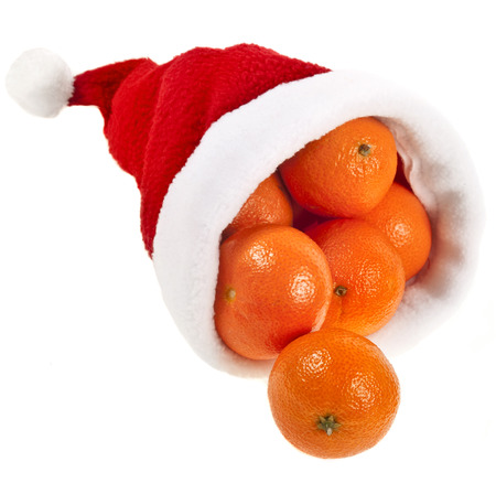 santa cap: Fresh ripe tangerines in a christmas hat isolated on a white background