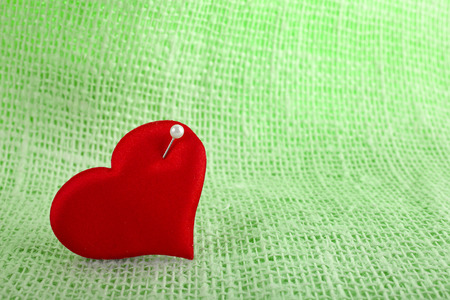 Valentine's day fabric sack texture background, red heart symbol with needle