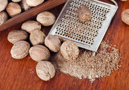 nutmeg: Ground nutmeg grated on wooden table background