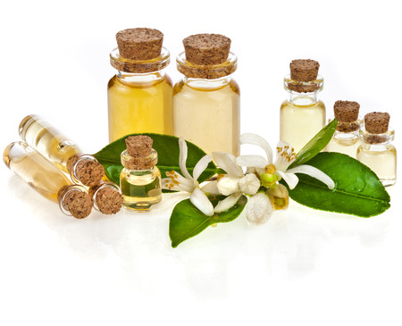 Herbal aromatherapy essential oil in bottles with fresh citrus flowers isolated on white Stockfoto