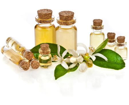 Pflanzliche Aromatherapie ätherisches Öl in Flaschen mit frischen Zitrus Blumen auf weiß isoliert