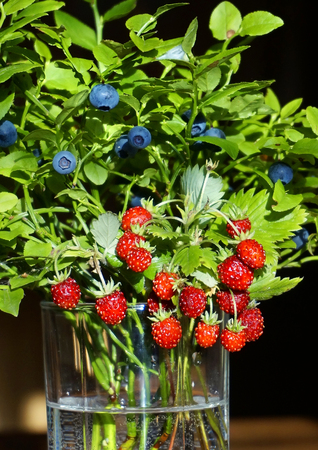 Bouquet of forest berries in glass vase