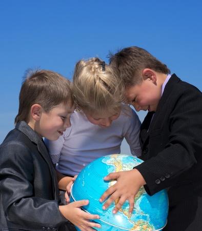 planeta tierra feliz: tres amigos sosteniendo la tierra globo en las manos, al aire libre de disparo