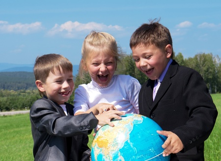 human geography: three happy friends holding earth globe, green meadow at background