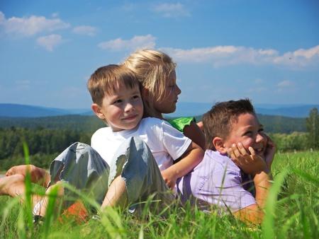 kid friendly: three happy friends play at summer meadow