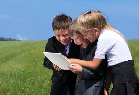 kids laptop: happy children with laptop, outdoor