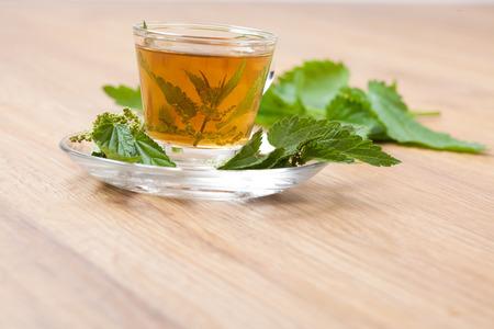 herbal tea made of stinging nettle, with nettle blossom inside teacup, wide shot, tilted, wooden floor,  photo