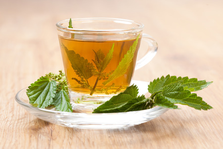 teacup full of nettle tea, with stinging nettle inside herbal tea, on wooden floor,