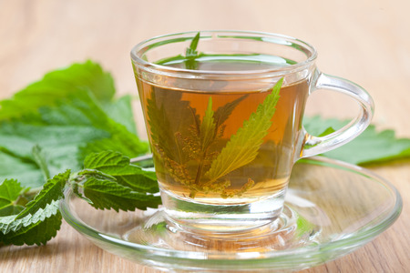 wide shot of medicinal nettle tea with fresh herbs inside teacup, stinging nettle leaves around, wooden floor,  Stock Photo