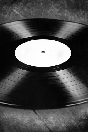 black and white version of vinyl record with white label, on wooden floor planks, retro vintage, textured,  photo
