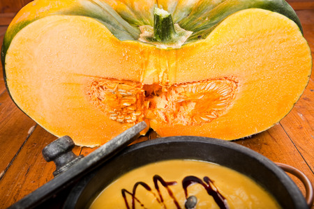 soapstone: fresh sliced ??pumpkin on old wooden flooring, pumpkin soup in soapstone bowl in front,