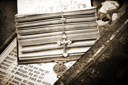 writ: vintage crucifix on opened ancient bible, textured background, sepia, Stock Photo