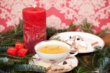 lighted: christmas tea in retro teacup, homemade christmas cookies, red lighted candle, christmas decoration
