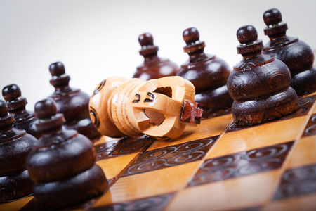 opposing: Chess King on wooden chessboard fallen down and checkmated, surrounded by opposing pawn