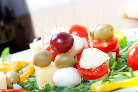 fingerfood: Fingerfood: skewers with cheese, olives, grapes, tomatoes on a plate with fresh rocket and sweet pepper, Stock Photo