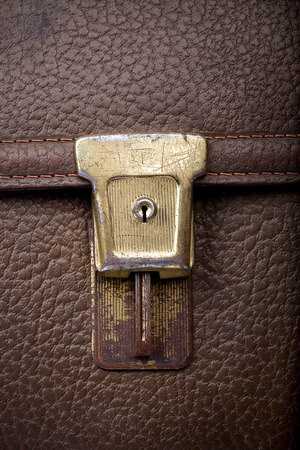 scratchy: old scratchy lock of used leather shool bag, closeup