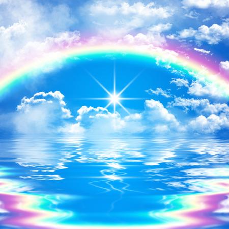 escena romántica del paisaje marino con el arco iris en el cielo nublado azul y el sol brillante, reflejo en el agua, con olas Foto de archivo