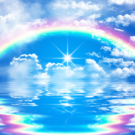 romantic seascape scene with rainbow on cloudy blue sky and bright sunshine, reflection in water, with waves